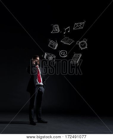Businessman talking on the phone over dark dramatic background. Business and office, concept.