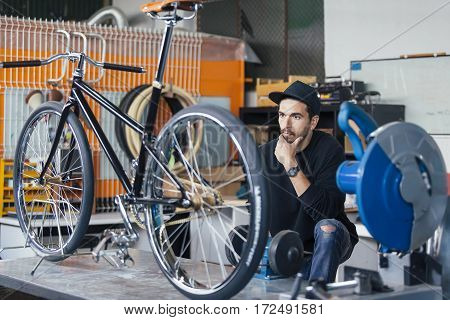 Bearded craftsman thoughtfully looking at handcrafted bicycle at workshop