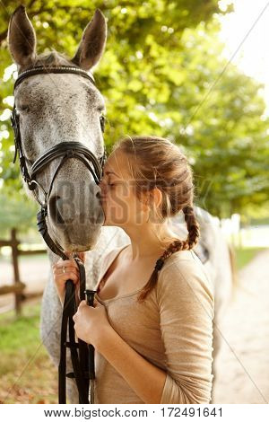 Young female rider kissing horse tenderly.