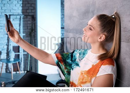 Young woman using mobilephone, making self portrait, smiling. Side view.