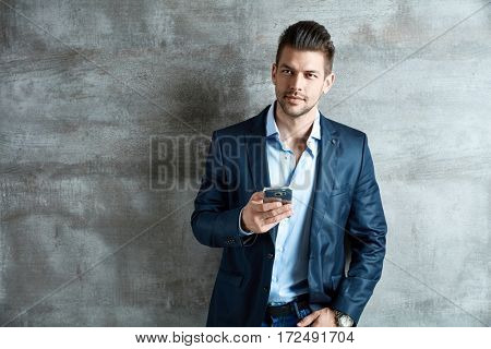 Portrait of a successful good-looking young businessman with mobile phone.