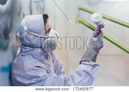 Side view of man in uniform and respirator painting bikes frame with green color