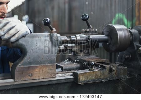 Craftsman working with iron lathe in motion