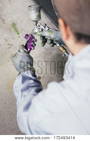 Unrecognizable man painting chassis of bicycle with purple color