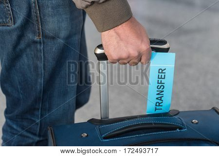 Close-up photograph of baggage with transfer label at airport with blurred background. Problems with transfer. Lost baggage
