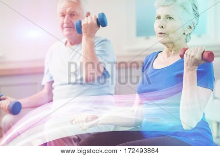 Senior couple lifting dumbbells while sitting at gym