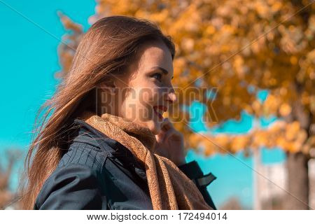 girl standing on the street in the Park, turning sideways close-up outdoors