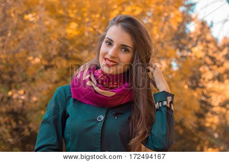girl in a handkerchief around her neck smiles and stands on the street