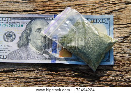 Marijuana in packet and 100 dollar bill on the wooden table