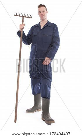 Young farmer with rake isolated on white background