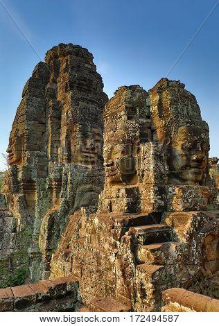 Giant stone faces at Bayon Temple at sunrise, Angkor Wat, Cambodia