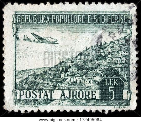 LUGA RUSSIA - FEBRUARY 7 2017: A stamp printed by ALBANIA shows airplane Douglas DC-3 over Yuno in Southern Albania circa 1950