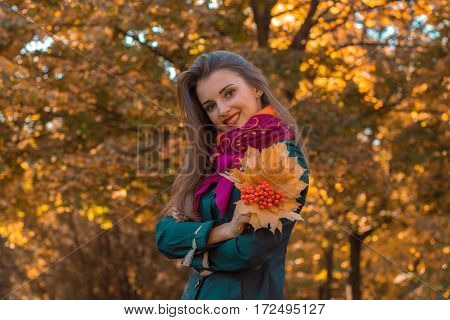smiling girl stands sideways on the street and keeps the dry leaves with Rowan