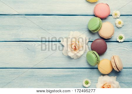 Colorful macaroons and flowers on wooden table. Sweet macarons. Top view with copy space for your text. Retro toned