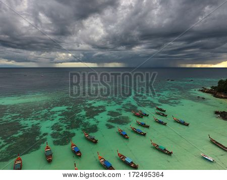 Long tail boats near tropical beach on the storm clouds background, Koh Lipe island, Thailand
