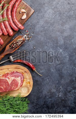 Sausages, meat and ingredients cooking. Top view on stone table with copy space