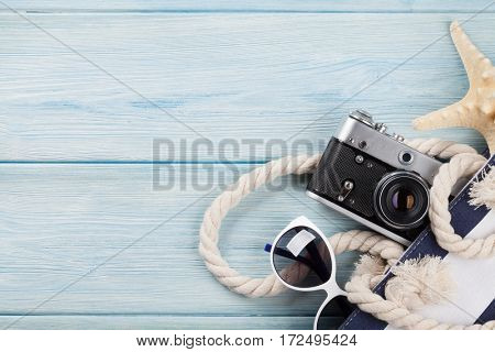Beach accessories. Bag with camera and sunglasses on wooden background. Top view with copy space.