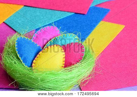 Handmade sisal nest with felt Easter eggs on colored felt sheets. Idea for Easter DIY decorations. Fun children Easter background. Closeup