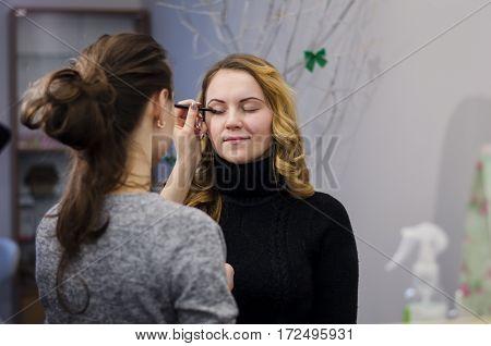 makeup artist apply makeup girl in the studio
