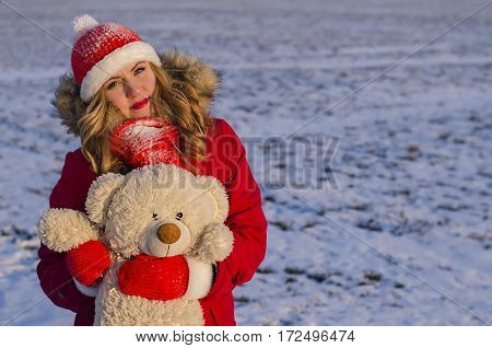 young girl in a red dress holding a teddy bear in his hands in the street