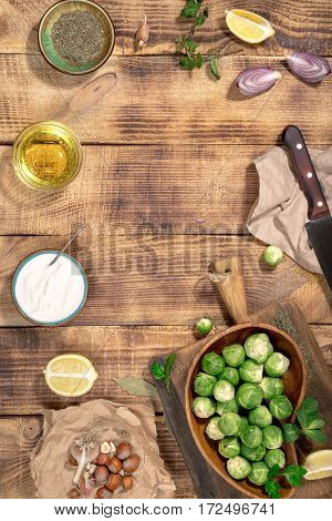 Frame of brussels sprouts with ingredients for cooking tasty and healthy food on wooden table top view. Healthy food