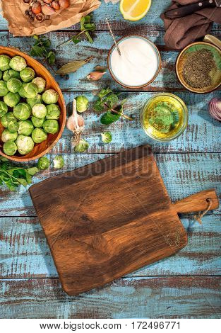 Wooden cutting board with brussels sprouts and ingredients for cooking healthy and delicious food on a blue wooden table top view. Healthy food