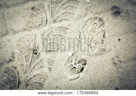 Shoe print and tyre track on a snow abstract background