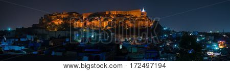 Glowing cityscape at Jodhpur at dusk. The majestic fort perched on top dominating the blue town. Scenic travel destination and famous tourist attraction in Rajasthan India.