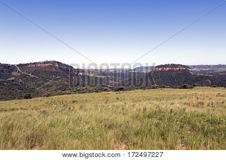 Grassland Against Distand Hills And Blue Sky Landscape