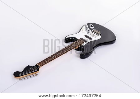 The classical form of black and white electric guitar lies horizontally with wooden maple neck isolated on white background.