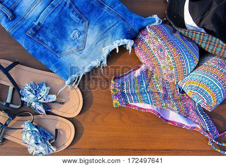 Set of beachwear on wooden background. Pink bikini jeans shorts sandals and hat.Summer holiday concept
