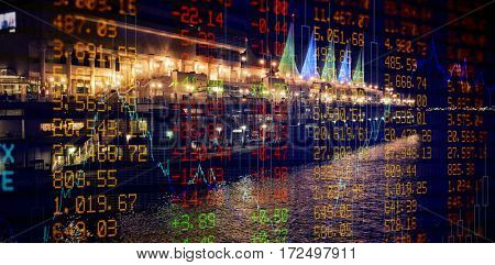 Stocks and shares against buildings by river in city at night