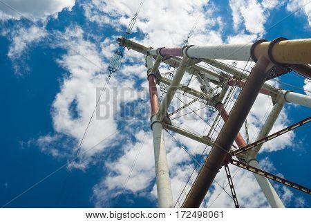Detail of electricity pylon against blue cloudy sky.