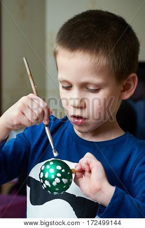 The boy paints on Christmas ball toy