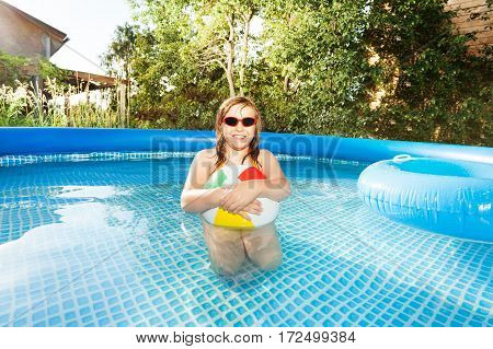 Portrait of cute girl in sunglasses playing with multicolored beach ball in swimming pool in the garden