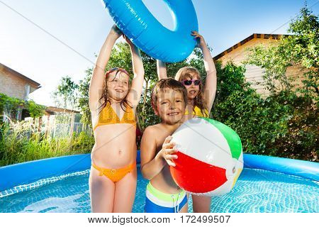 Portrait of cute kids playing with wind ball and swim ring in big inflatable pool outside