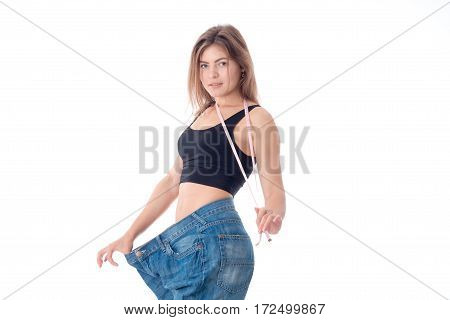 slender girl keeps Roulette and stands on a large denim pants isolated on white