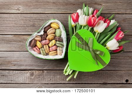 Colorful tulips bouquet and gift box with macaroons on wooden background. Red and white. Top view