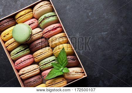 Colorful macaroons in a gift box on stone table. Sweet macarons. Top view with copy space