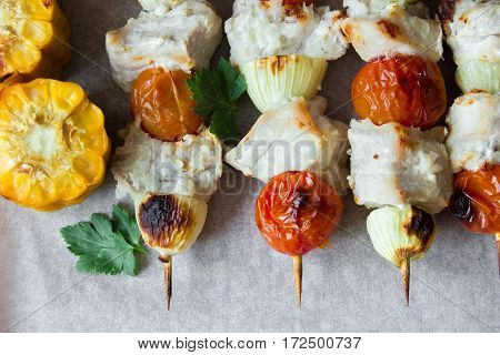 Skewered on wooden sticks tasty pork meat and vegetables mix, on wooden background. horizontal