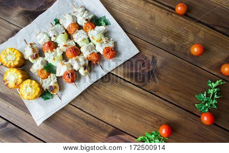 Skewered on wooden sticks tasty pork meat and vegetables mix, on wooden background. horizontal. space for text
