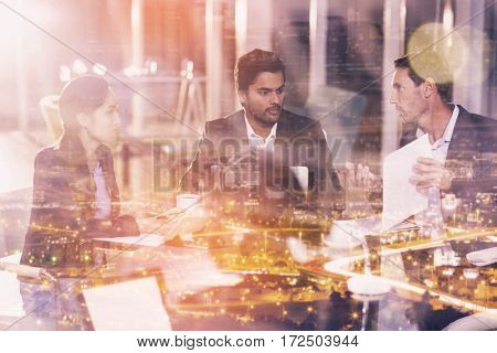 High angle view of illuminated cityscape against group of businesspeople interacting with each other