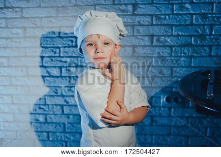 Child with kitchen spoon, dressed as a cook