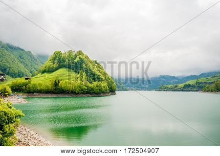 Beautiful emerald mountain lake Lungern in Switzerland under low clouds