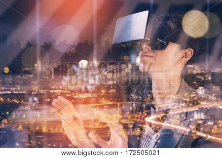 High angle view of illuminated cityscape against businesswoman using virtual reality headset
