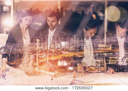 High angle view of illuminated cityscape against group of businesspeople discussing over document while standing