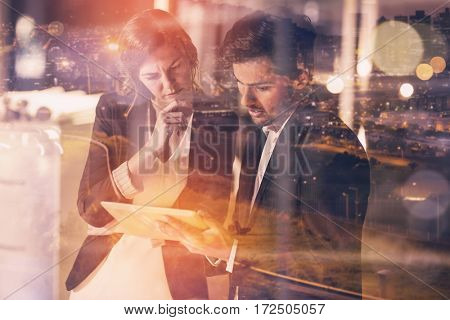 High angle view of illuminated cityscape against businessman discussing with colleague over digital tablet