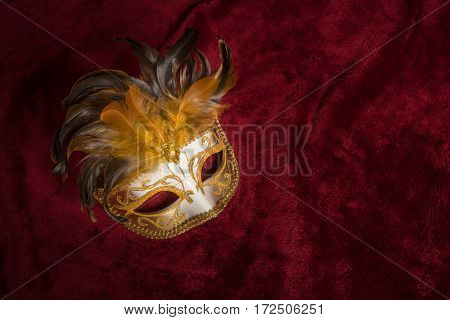 Brown golden venetian carnival mask with feathers seen from above on a draped red velvet theater curtain