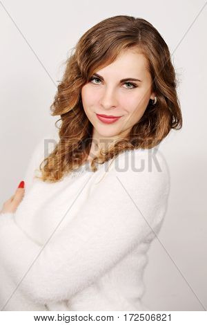 Beautiful woman in white pullover on a white background