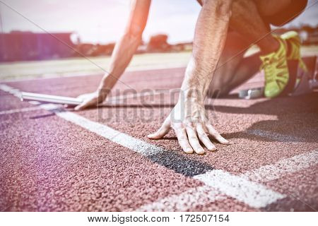 Athlete ready to start the relay race on running track